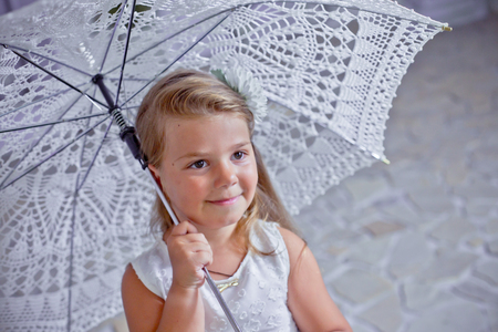 Sad girl with lace umbrella. child thought. Lovely girl in white dress.