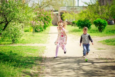 Brother and sister run along a path along flowering trees in spring. Active childrens games on the street. Little beautiful boy plays with an adult girl in a ball on the nature.