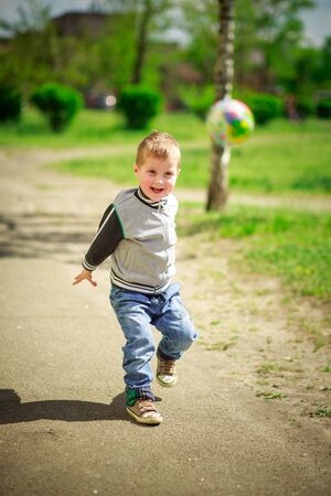 A little handsome boy widely smiling throws the ball forward. Happy child on a walk without gadgets. Active spring games outside in good weather.