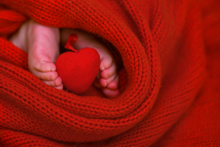 Red heart on baby legs. legs of the newborn on a red background. baby wrapped in a red blouse. Valentine's Day 版權商用圖片