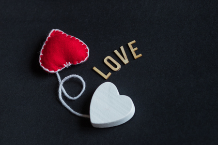 Happy Valentines Day romantic greeting card. red heard from felt and white wood hearts. Handmade heart on black background. Text Love. Place for text, copy space.