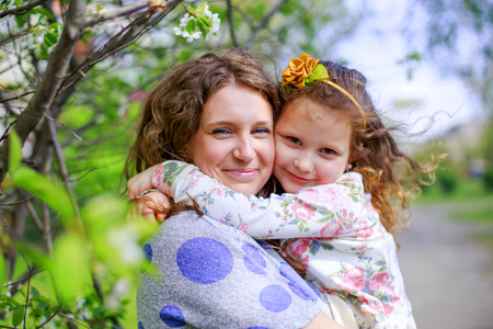 Daughter hugs mom. Happy woman holding little girl in arms. Beautiful mother with daughter on Mothers Day. childs hands clasped moms neck.