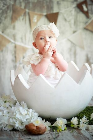 cute beautiful emotional baby sitting in easter egg on background of flags and eats an egg. Little one year old girl in white dress celebrates Easter. Stock Photo - 132634386