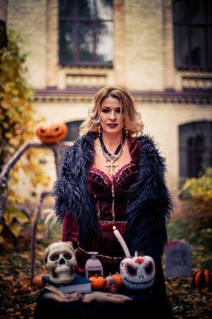 woman in witch's costume is conjuring. Table of sorceress with skulls and pumpkin decorated for the day of dead. Halloween celebration in costume.