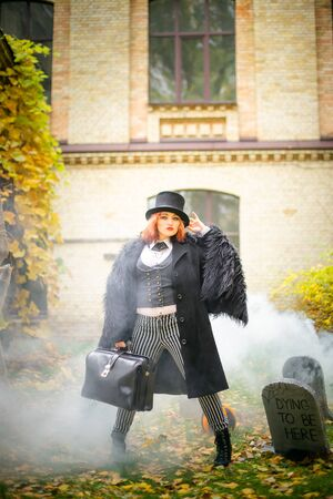 woman in cap and with redicle against background of cemetery. Tombstone in fog for Halloween. day of Dead Standard-Bild - 132237152