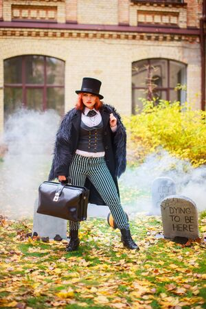 woman in cap and with redicle against background of cemetery. Tombstone in fog for Halloween. day of Dead 写真素材