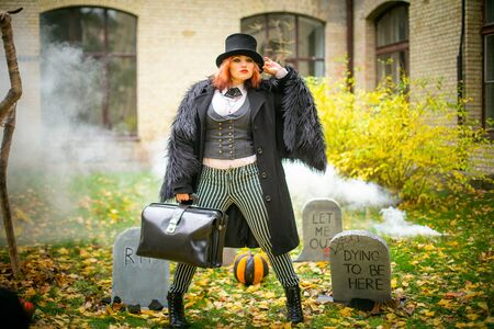 woman in cap and with redicle against background of cemetery. Tombstone in fog for Halloween. day of Dead Standard-Bild - 132237656