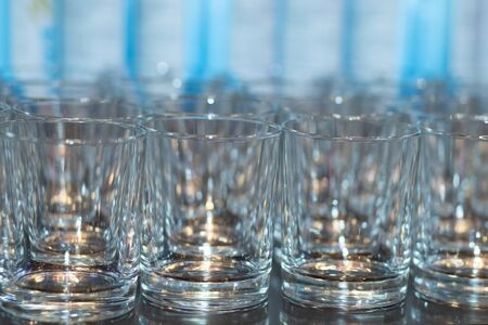 A row of empty glasses for vodka. Small piles for water. Banquet preparation.