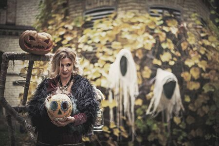 Beautiful woman in witch costume holds pumpkin painted in ack-o-lanterns style. Steaming pumpkin in decor for Halloween. Sorceress on background of ghosts.