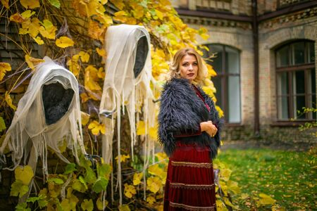 Beautiful woman in a witch costume stands on a background of ghosts. Stylized Halloween decor. 写真素材