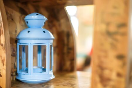 Lonely lantern on shelf in cafe. Decor of restaurant with natural materials