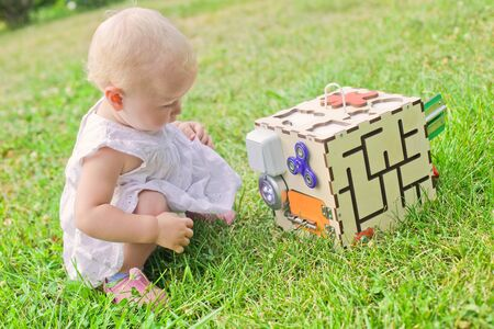 Cute little girl is playing with busiboard outdoors on green grass. Educational toy for toddlers. girl opened door to cube of board