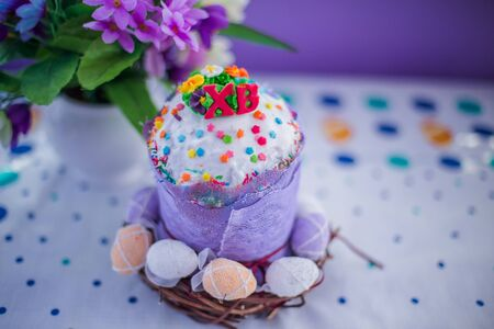 cake on table for Easter. Purple and white eggs around cake. Easter background