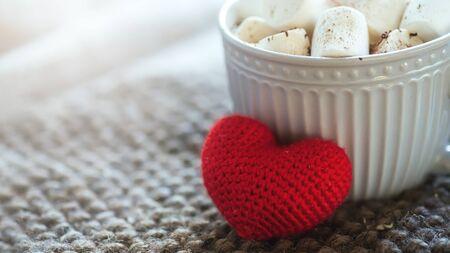 Hintergrund mit grauer Tasse mit Marshmallows und rotem Herzen auf gestrickter Serviette. warmes Getränk mit grauem Schal .. Valentinstag Konzept, Tasse Kaffee
