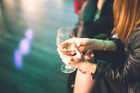 A glass of wine in the hands of a young girl dressed as Leather jacket. Celebration party in rock style at a cafe. Soft focus Фото со стока