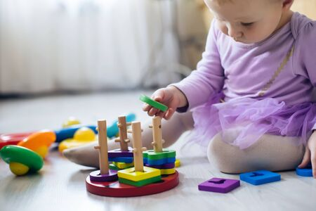 girl plays toys in living room. Montessori wooden toy folded pyramid. Circle, quadra, triangle, rectangle wooden elements of children's toys. Multi-colored toy blue, yellow, red, green.