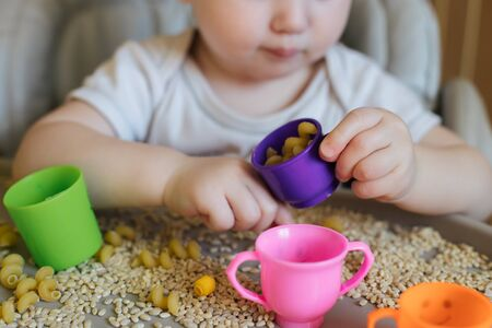 child chooses dry pasta from wheat grains. Sorting products. Logical games with children. concept of early development of children up to a year.