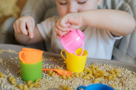 small kid sits on feeding chair and plays with toy utensils and grain. development of fine motor skills in children up to year. Early development Banque d'images