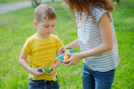little boy shares Easter eggs with his sister. girl and a boy hold eggs against grass. holiday and child concept