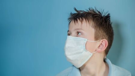 boy in medical mask turned sideways and looked up. child with flu, influenza or cold protected from viruses, among patients with coronavirus. Reklamní fotografie