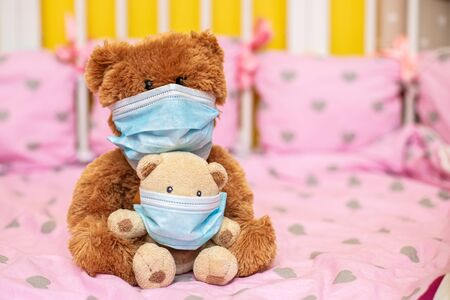 large teddy bear in protective mask and small teddy bear in medical mask sit in cot. Sick animals during epidemic. Coronovirus, quarantine, pandemic, flu, cold,illness. Medicine concept and health.