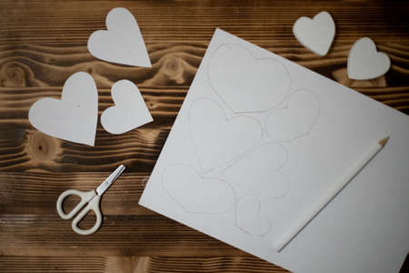 Hand-carved diy hearts made of white copy paper. Preparation for crafts for Valentine's Day. Gift ideas for Valentines Day, day love, concept of February 14. Step by step. process crafts. Valentine card.