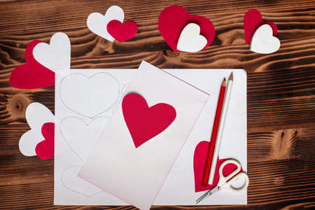 Valentines diy. Step by step instructions for handmade valentine. Craft gift, flat lay. Step 4. Heart of red paper. Preparation for creation of valentine, paper garland of hearts, postcard