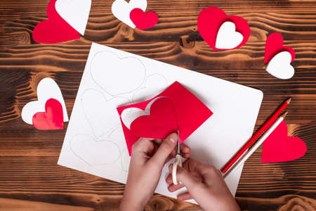 Valentines diy. Step by step instructions for handmade valentine. Craft gift, flat lay. Step 3. Cut your heart out of red paper, along lines Banco de Imagens