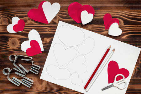Valentines diy. Step by step instructions for handmade valentine. Craft gift, Valentines day card, flat lay. Step 1. Draw heart cut patterns on white paper
