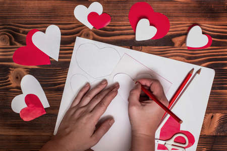 Valentines diy. Step by step instructions for handmade valentine. Craft gift, flat lay. Step 2. Circle the pattern by transferring the drawing of heart to red paper. Draw from the back.