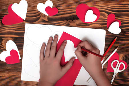 Valentines diy. Step by step instructions for handmade valentine. Craft gift, flat lay. Step 2. Circle the pattern by transferring the drawing of heart to red paper Banco de Imagens