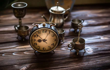 Clock on wooden background. Alarm. Hurry up. Rush. Time. Little time. silver vintage checker on a table lit by the rising sun. Preparing for the work day. 免版税图像