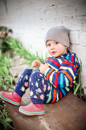 little funny girl in striped jacket sits next to brick wall of the house. child walks in yard. Walking in all weathers 免版税图像