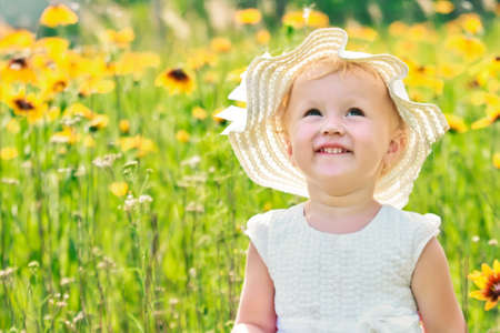 little girl in hat laughs happily on yellow flowers background in meadow in nature. Walking while quarantine away from people. Happy childhood concept 免版税图像