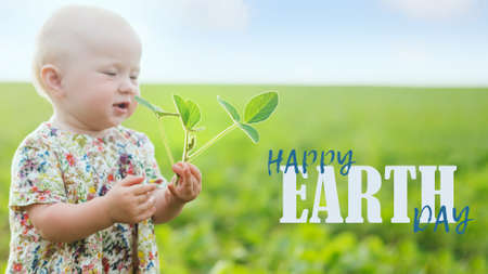 little girl holds young soybean sprout. Text HAPPY Earth Day. Sustainable environment, plant Glycine max, soybean, soya bean sprout growing soybeans on an industrial scale 免版税图像
