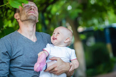 Father's Day. Dad with smiles daughter in arms. family young daddy and small cute child, Happy childhood.