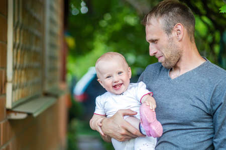 father holds daughter of one year old in arms. Daddy's love for girl. child is having fun outdoors on summer day. Family activity. Toddler smiles