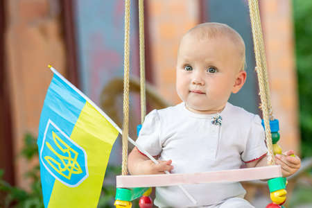 baby with Ukrainian flag sits on swing in park on walk. Child celebrates Ukraine's independence day at home