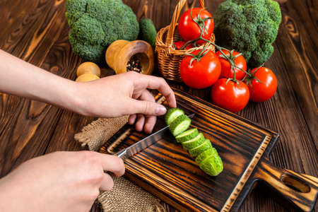 chef's hands chopping cucumber on a cutting board. Fresh vegetables and dry buckwheat on a wooden table. Organic farmers products. Broccoli, tomatoes, cucumbers from market. Healthy food concept