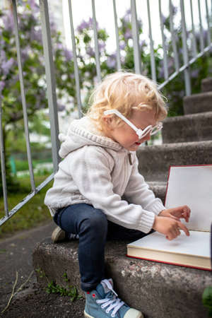 Back to school. Smart little girl reads a big book. child sits on the steps of school with glasses. Open textbook in front of child. 免版税图像