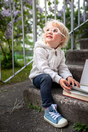 A girl with glasses sits next to an open book. Pre-school education. Funny baby in a knitted jacket and sneakers