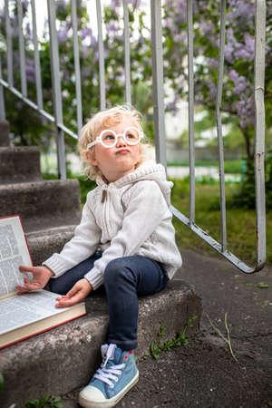 little girl reads a big book. encyclopedia lies on steps of the school. Getting knowledge by children in kindergarten. Kid looks up 免版税图像