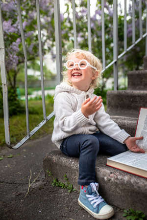girl with glasses laughs. child reads funny book sitting on steps of a school. Portrait of a preschool girl in white sweater. Early education for children under three years of age.