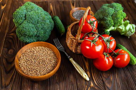 Fresh vegetables and dry buckwheat on a wooden table. Organic farmers products. Broccoli, tomatoes, cucumbers from market. Proper nutrition concept. Healthy food