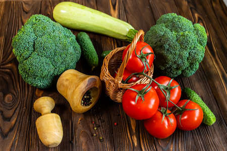 Fresh vegetables and mixture of peppers in a wooden mortar. Organic farmers products. Broccoli, tomatoes, cucumbers from market. Proper nutrition concept. Healthy food 免版税图像