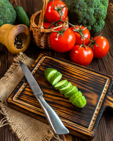Fresh cucumber cut into slices on cutting board. Prepare ingredients for salad. Fresh vegetables on table. Organic farmers products. Broccoli, tomatoes, cucumbers from market. Healthy food concept