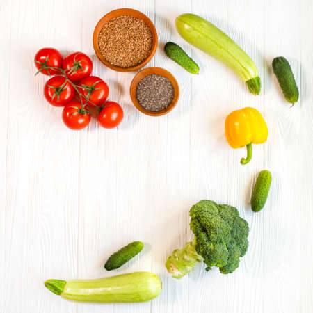 Fresh vegetables on a white background. Dietary products on a wooden table. Cucumbers, broccoli, tomato, zucchini and porridge in a wooden plate. Reklamní fotografie