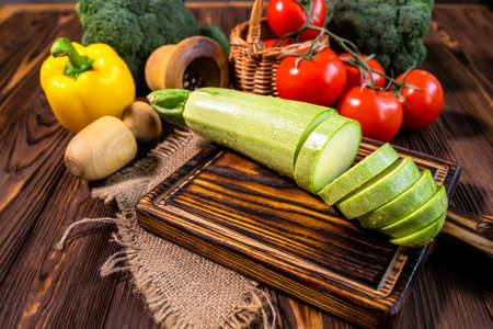 Sliced courgette on a cutting board. Assortment of healthy food ingredients for cooking on a wooden table