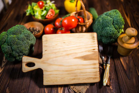 A cutting board with copy space. Mock up. A place for the restaurant's menu. Mix of colorful assorted fresh vegetables. Balanced nutrition concept for diet 免版税图像