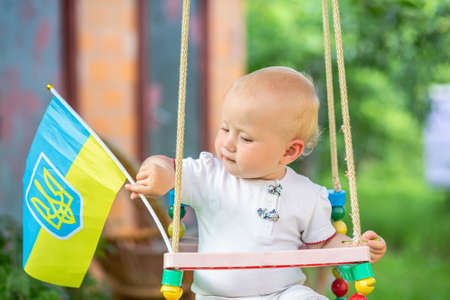 A little girl on a hanging swing with the flag of Ukraine. Independence Day of Independence Ukraine and Kiev Day.